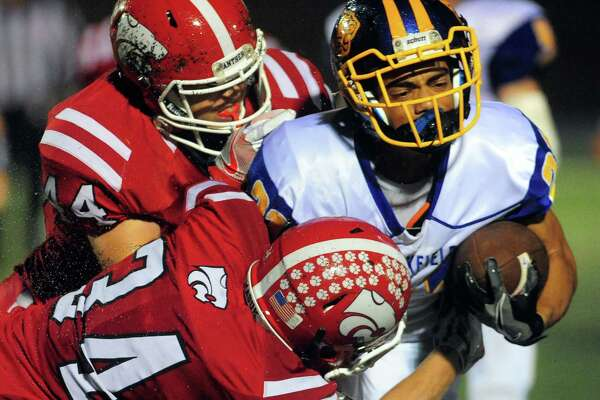 Brookfield's Samuel Jackson is taken down by Masuk's Andrew Ciancetta, top left, and Jack Roberge during football action in Newtown, Conn. on Friday Sept. 30, 2016.