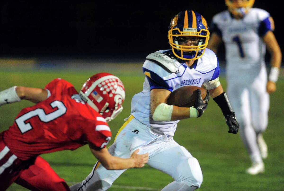 Brookfield's Conor McVey, right, tries to dodge Masuk's Ryan Shaw during their football game Friday night at Newtown High.