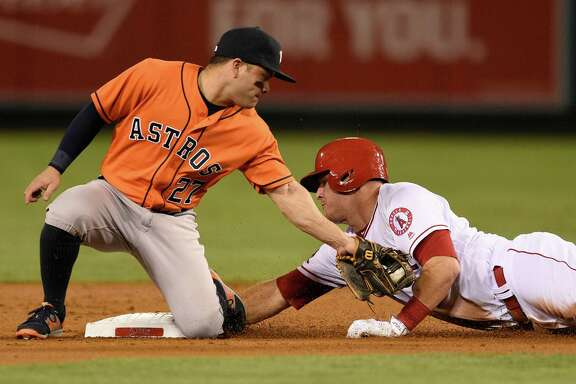 The Angels' Mike Trout, right, beats Astros second baseman Jose Altuve's tag to the bag in the first inning Friday night in Anaheim, Calif. Altuve got his 213th hit of the season and Trout his club-record 114th walk during the Angels' 7-1 victory.