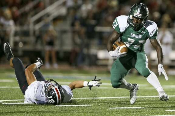 Reagan's Marquis Duncan runs past Churchill's Grant Gomez during the first half of their District 26-6A game at Comalander Stadium on Sept. 30, 2016.