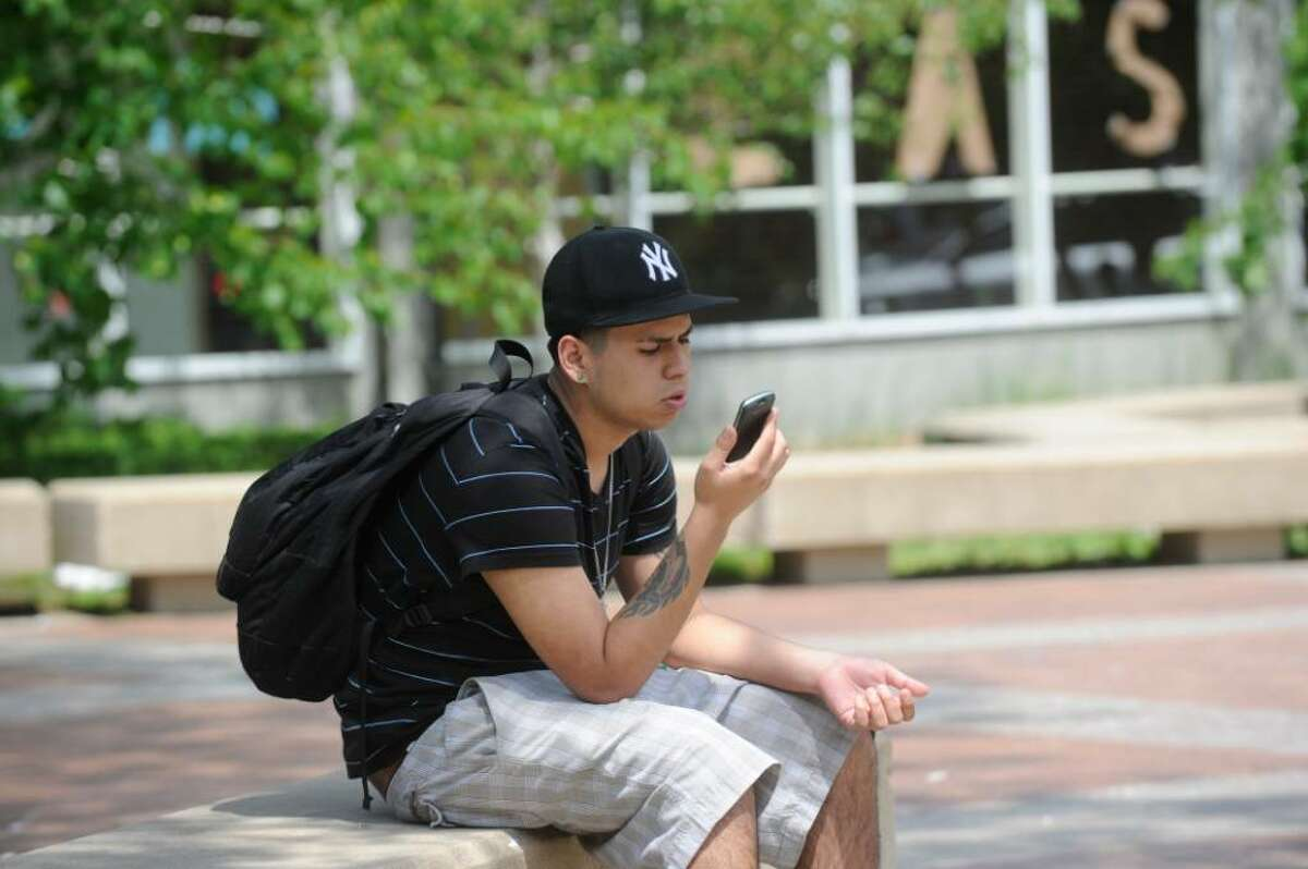 Paola Serpa, 18, a senior at Greenwich High School, uses his cell phone outside the school.
