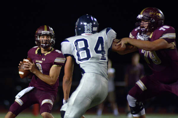 Magnolia West quarterback John Matocha, left, tries to locate a target behind Tomball Memorial defender Benjamin Batts, who had a pick-six in Friday's game.