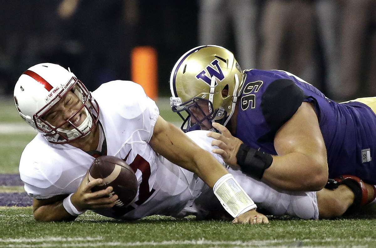 Stanford quarterback Ryan Burns, left, reacts after being sacked by Washington defensive lineman Greg Gaines in the first half of an NCAA college football game, Friday, Sept. 30, 2016, in Seattle. (AP Photo/Ted S. Warren)