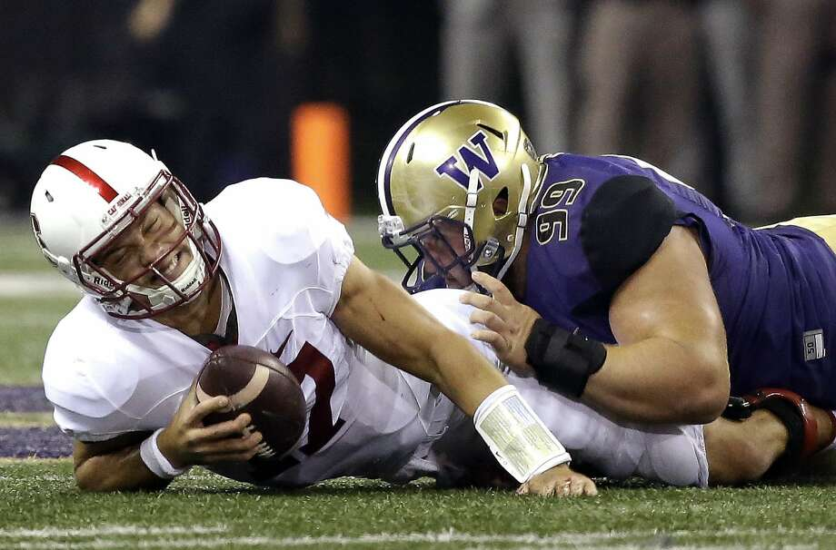 Stanford quarterback Ryan Burns, left, reacts after being sacked by Washington defensive lineman Greg Gaines in the first half of an NCAA college football game, Friday, Sept. 30, 2016, in Seattle. (AP Photo/Ted S. Warren) Photo: Ted S. Warren, Associated Press