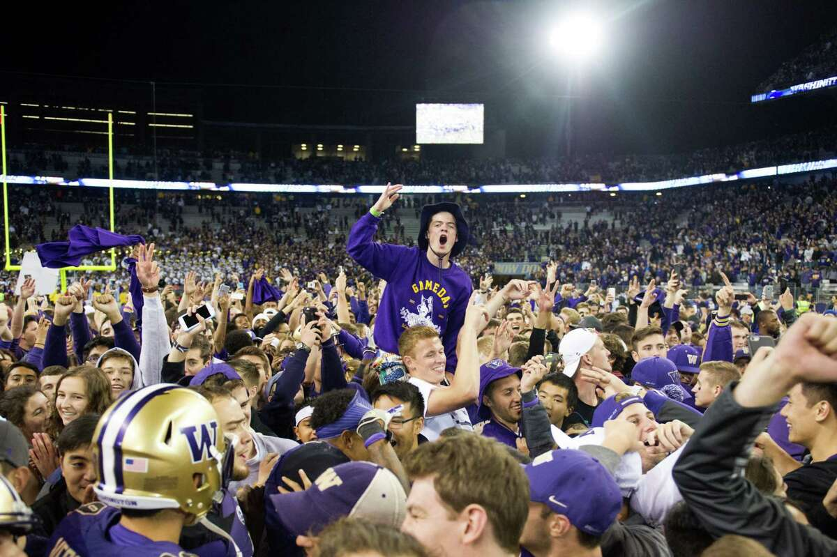 Students and fans rush the field following University of Washington's 44-6 victory over Stanford at Husky Stadium. The Huskies remain undefeated 5-0