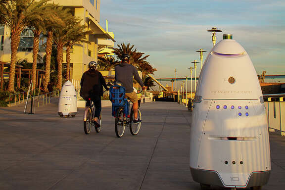 Knightscope K5 security robots patrol alongside a pier, in San Diego. The robots can sense intruders at odd hours.