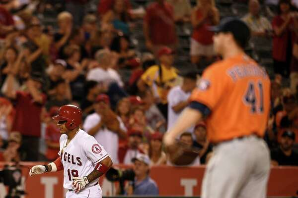 Los Angeles Angels' Jefry Marte, left, runs the bases after hitting a solo home run off Houston Astros starting pitcher Brad Peacock, right, during the third inning of a baseball game in Anaheim, Calif., Friday, Sept. 30, 2016. (AP Photo/Kelvin Kuo)