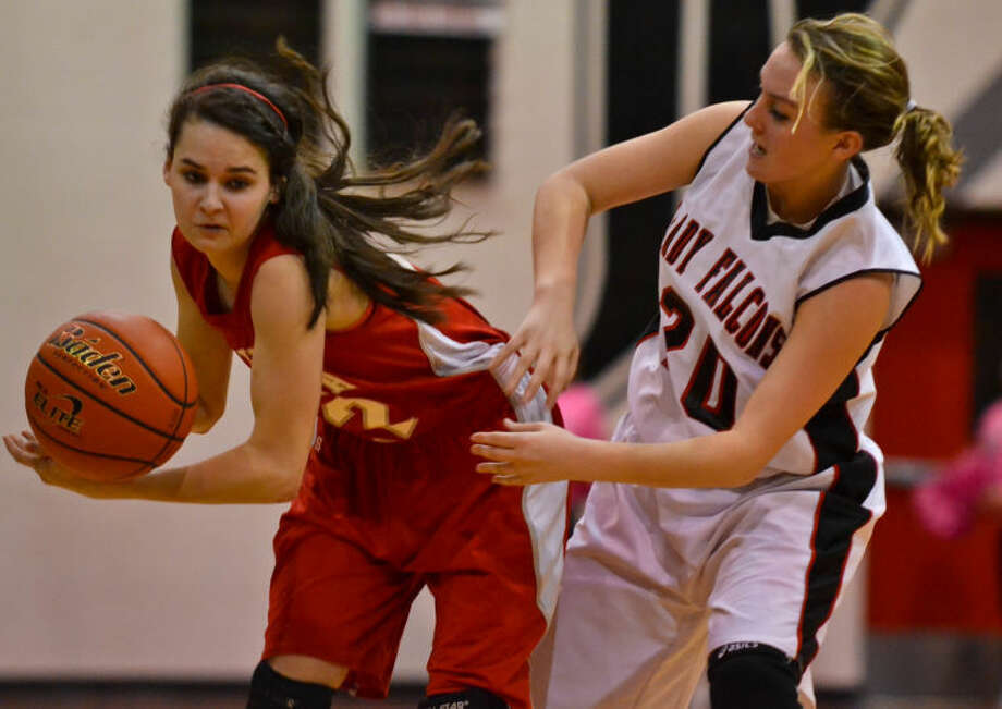Kayla Pendergrass (right) tries to strip the ball loose from Frankie York during the third quarter of Huffman's 63-37 win over Splendora in a District 22-3A girls basketball game on Feb. 5, 2013.