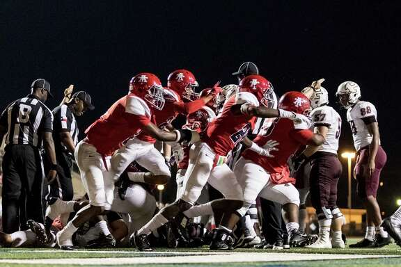 Members of Alief Taylor's defense celebrate after stopping Pearland on fourth down at the goal line Friday night. Alief Taylor won 19-14.
