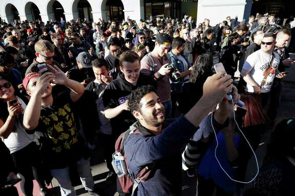 """FILE - In the Wednesday, July 20, 2016, file photo, """"Pokemon Go"""" players begin a group walk along the Embarcadero in San Francisco. """"Pokemon Go"""" was an instant hit when it debuted in July, as millions of people discovered augmented reality and joined stampedes from Central Park to Sydney capturing Pokemon via their phones. But as the hype subsides, what's next for the game? (AP Photo/Marcio Jose Sanchez, File)"""