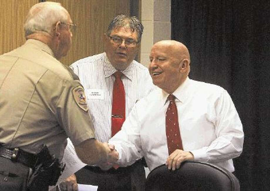 U.S. Rep. Kevin Brady, R-The Woodlands, shakes hands with Precinct 2 Constable Chief Deputy Steve Roper, left, and Precinct 2 Constable Gene DeForest, middle, at a roundtable Thursday at the Montgomery County Sheriff's Office. / @WireImgId=2625948