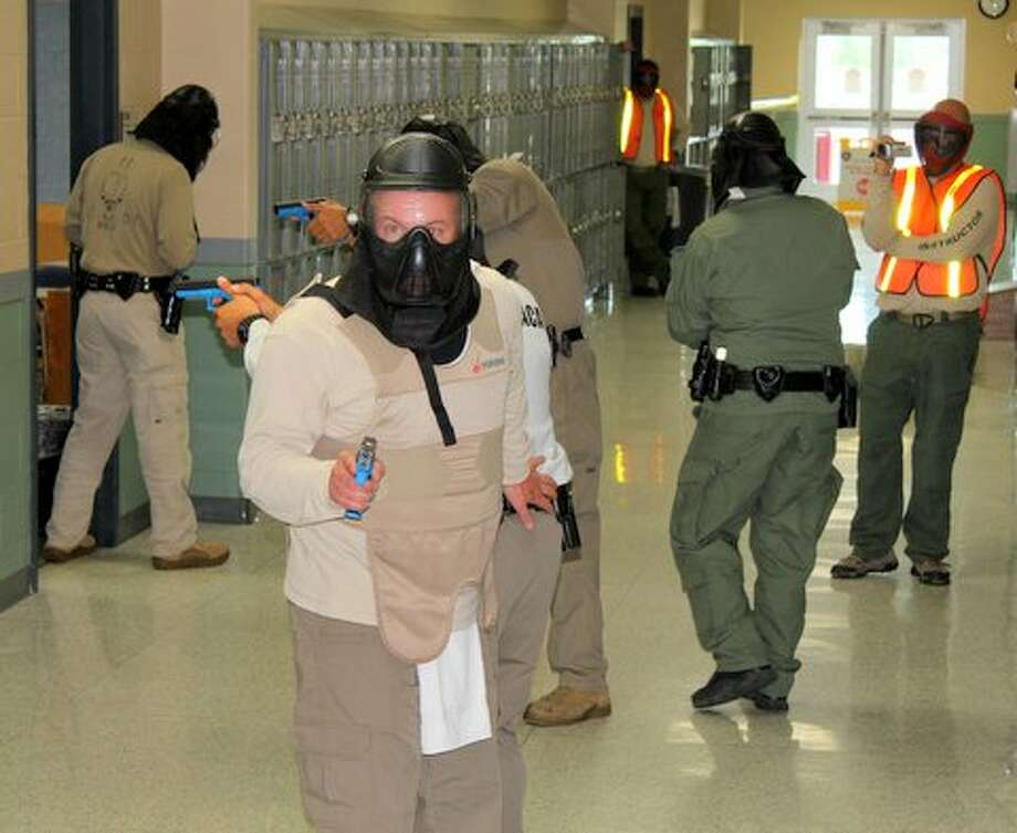 Officers in the ALERRT class used simunitions, non-lethal training ammunition during exercises at Fort Bend ISD's Travis High School last week. In this photo, officers are clearing classroom by classroom as they proceed down a hallway. Instructors in orange vests, back right, film the exercise to use in after-action reviews.