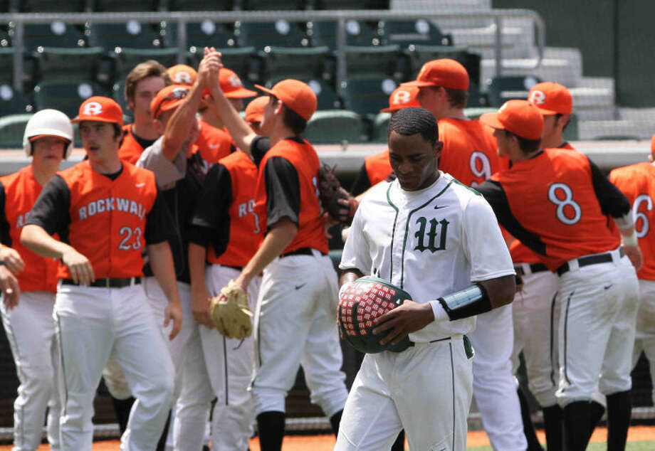 8f61ccc4276 The Woodlands Kolbi Brown walks off the field as Rockwall players celebrate  after defeating The Woodlands