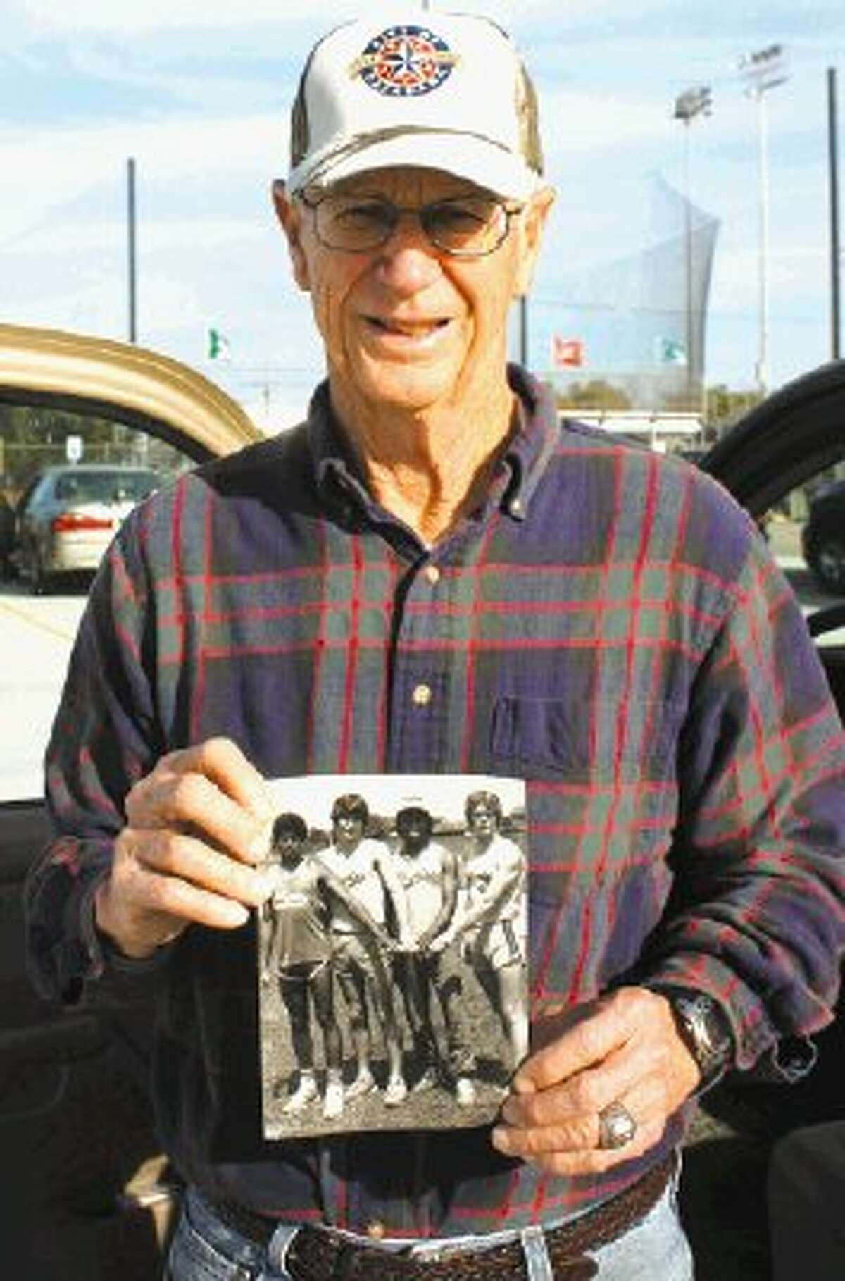John Bryan holds the picture to one of his Dobie relay teams that gave the soon-to-be PISD Sports Hall of Fame inductee one of his many triumphs. Bryan, who coached track and field at Queens, Pasadena and Dobie, guiding the Longhorns to two 5A state titles during the 1980-81 school year, will be inducted April 13 along with seven others.