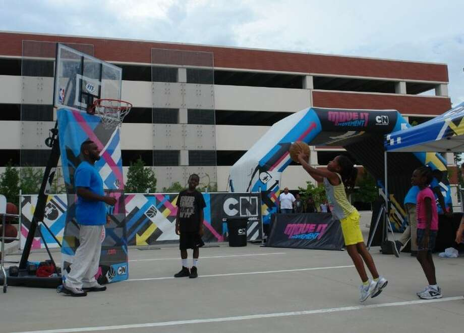 """A youngster shoots some hoops Sunday afternoon at Cartoon Network's """"Move It Movement"""" Tour at Sam Houston State University The Woodlands Center. The NBA Hoop Troop was one of several activities designed to promote fitness and nutrition for children while also offering a chance for parents to meet with SHSU representatives regarding education opportunities."""