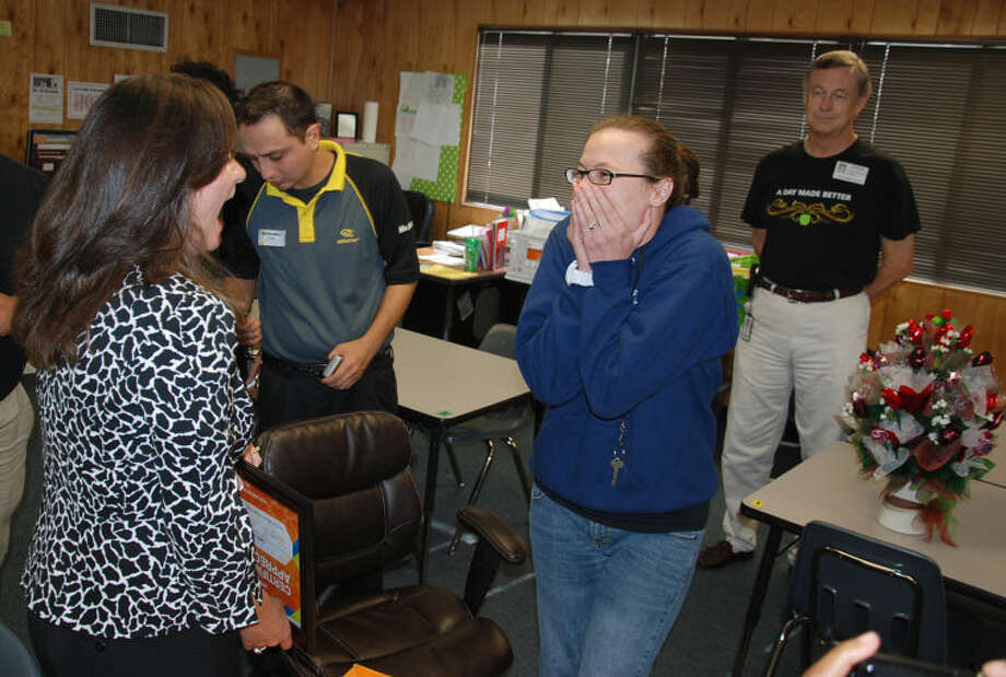 Hopper principal Wendi Witthaus celebrates the surprise donation from OfficeMax with teacher Callie Jones on Tuesday.