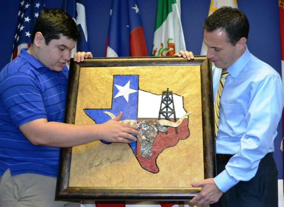 "Award-winning eco-artist Grant Manier, 17, shows Deputy District Director Russell Martinez, with U.S. Rep. Kevin Brady's office, the concept of his ""Texas, Our Texas"" collage. The original piece of art displays a longhorn, oil derrick and lone star within the state of Texas using more than 3,000 recycled materials. The piece will be placed in the Capitol in Washington, D.C., for one year."
