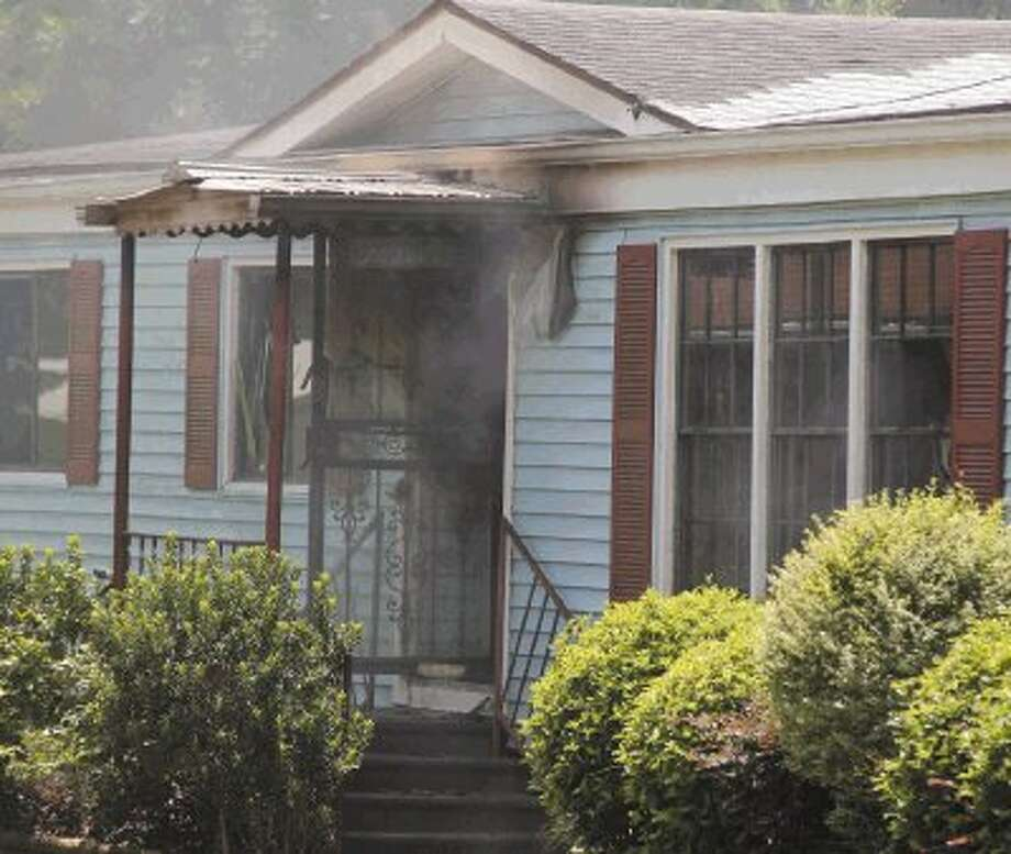 Light smoke comes out of the house after fire burned much of it on Lily Street Monday afternoon.