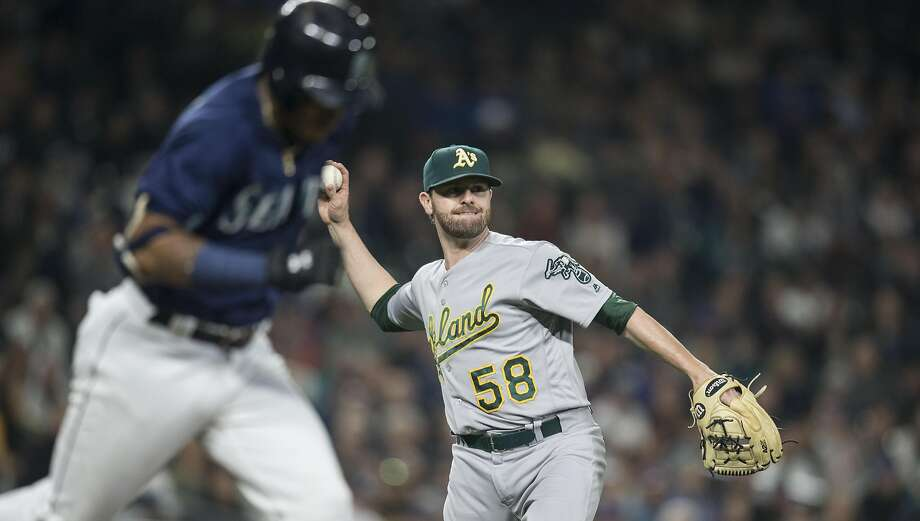 SEATTLE, WA - SEPTEMBER 30: Relief pitcher Zach Neal #58 of the Oakland Athletics throws to first for a put out after fielding a ball hit by Ketel Marte #4, left, of the Seattle Mariners during the fourth inning of game at Safeco Field on September 30, 2016 in Seattle, Washington. The Mariners won the game 5-1. (Photo by Stephen Brashear/Getty Images) Photo: Stephen Brashear, Getty Images