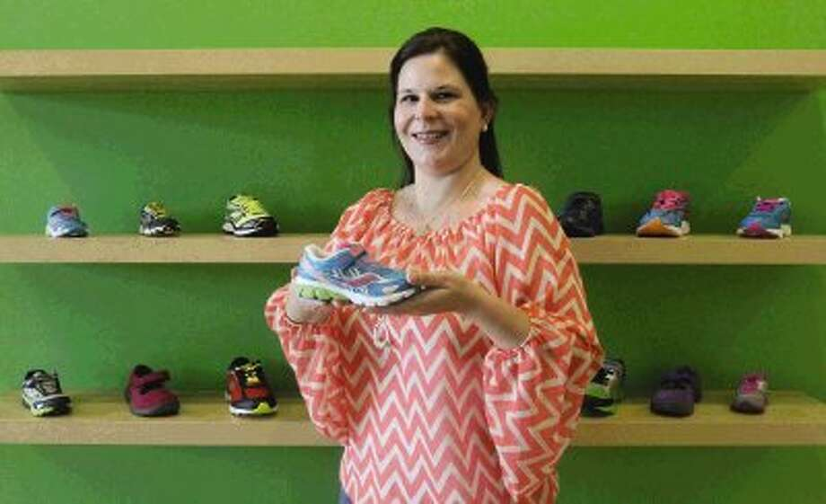 Owner Kay Mehrens poses for a portrait at her shoe store called 'Walking Tots.' The store sells shoes for newborns through 10 years of age. / Conroe Courier