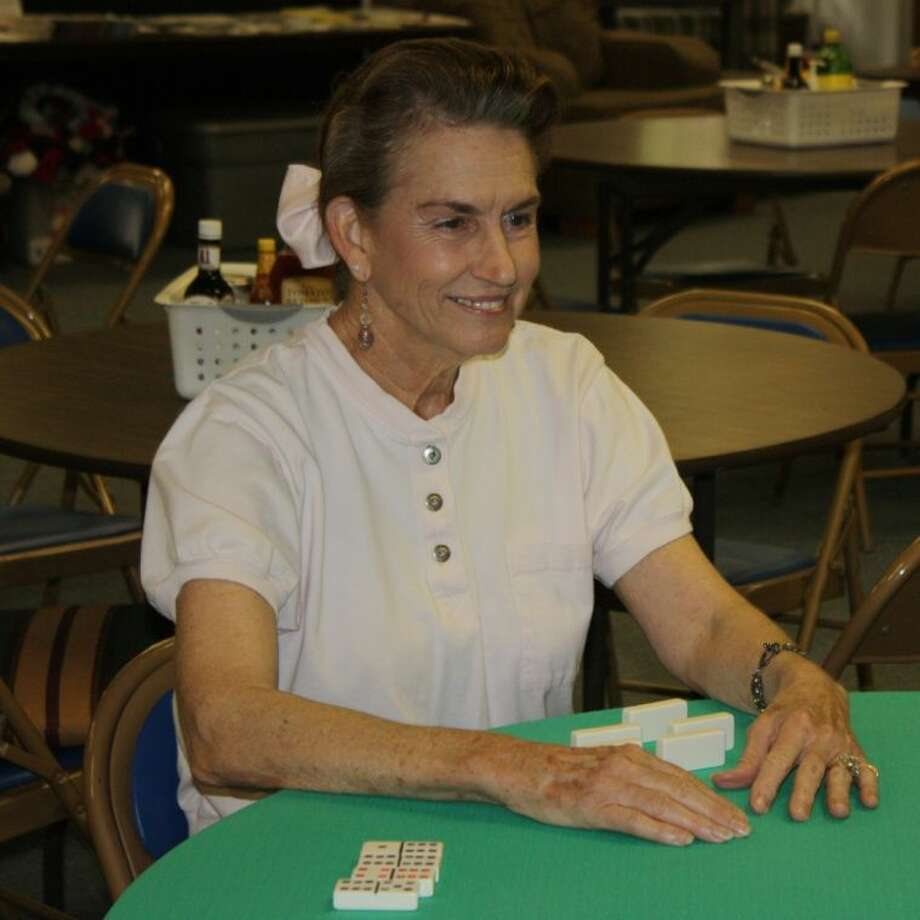 Paula Williams, one of the aerobics instructors at the Coldspring Senior Citizens Center, plays a game of dominoes with friends shortly before lunch. The center is a popular place for seniors to fellowship with one another and to stay involved with the community.