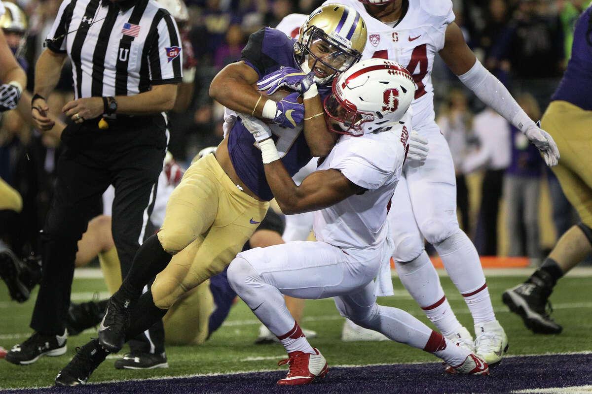Washington running back Myles Gaskin pushes through Stanford safety Justin Reid at Husky Stadium, Friday, Sept. 30, 2016.