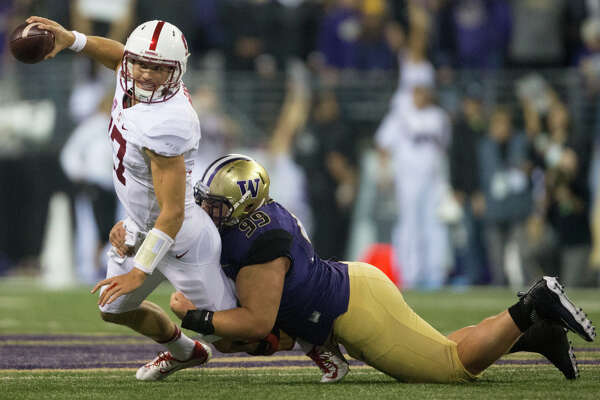 Stanford quarterback Ryan Burns is stacked by Washington defensive lineman Greg Gaines at Husky Stadium, Friday, Sept. 30, 2016.