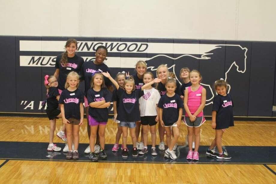Kingwood High School cheerleaders teach some aspiring cheerleaders at a youth cheer fundraiser.