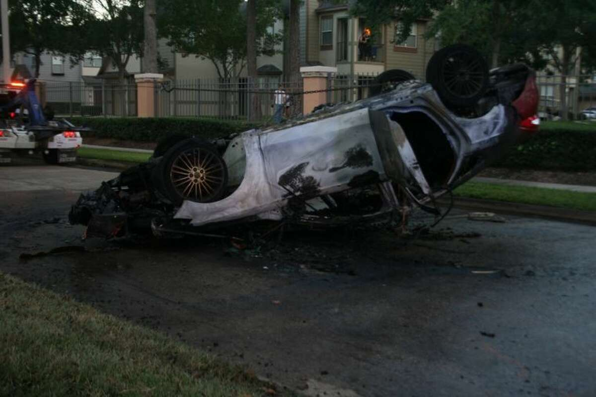 An red Ford sedan caught on fire after striking a tree.