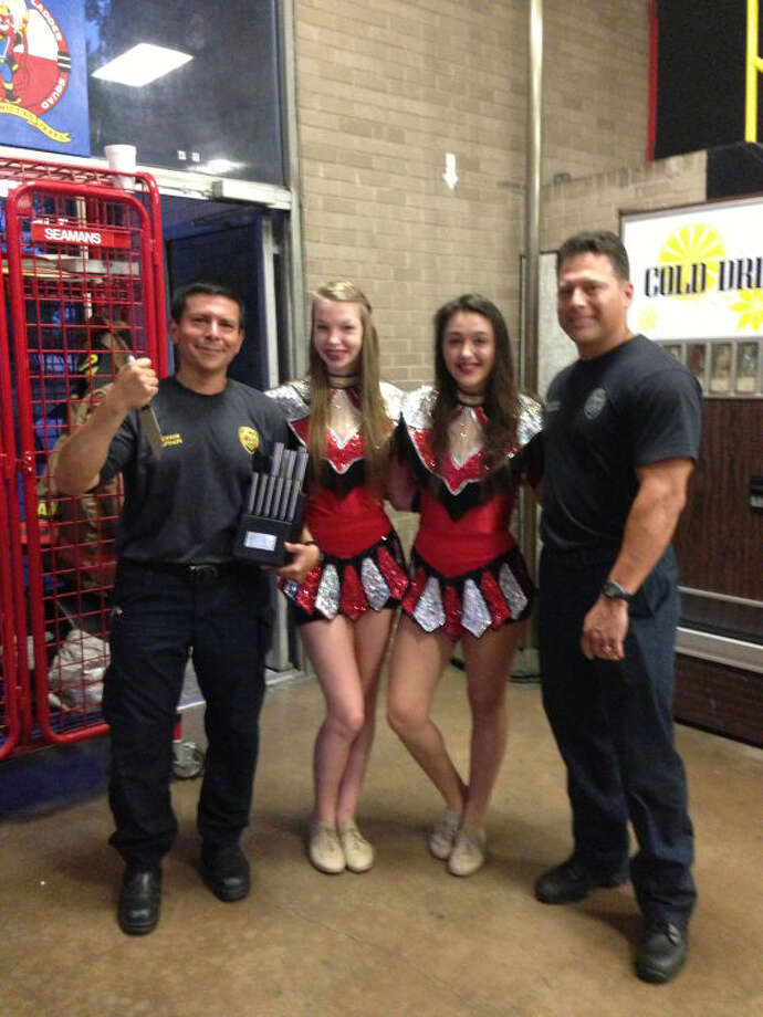 Cypress Lakes High School Sterling Star members Sarah Ellis and Hope Owens present a cutlery set to a pair of firefighters from HFD Station No. 51 during a service project on the 12th anniversary of 9/11.