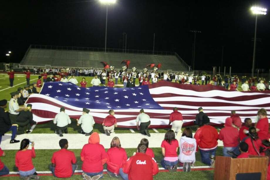 Members of the Crosby JROTC program unfurled a giant American flag at the Red, White and U night at Cougar Stadium in Crosby.