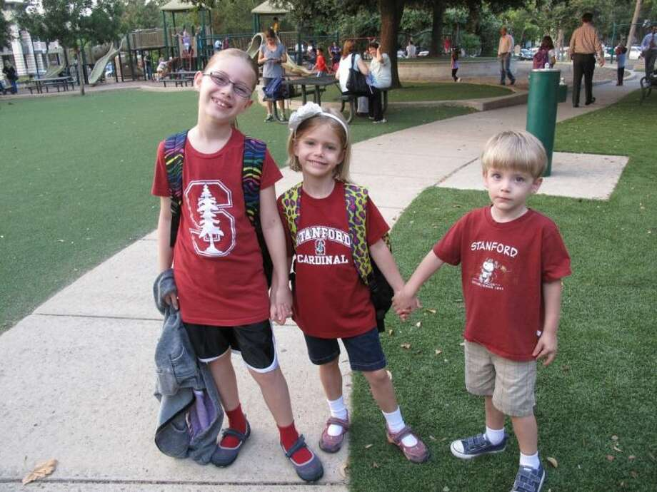 Third grader Taryn Morris, Kindergartner Devin Morris, and future West University Elementary Mustang Dean Morris show off their future school pride during the annual College Colors Day. West University Elementary participates in College Colors Day to promote higher education.
