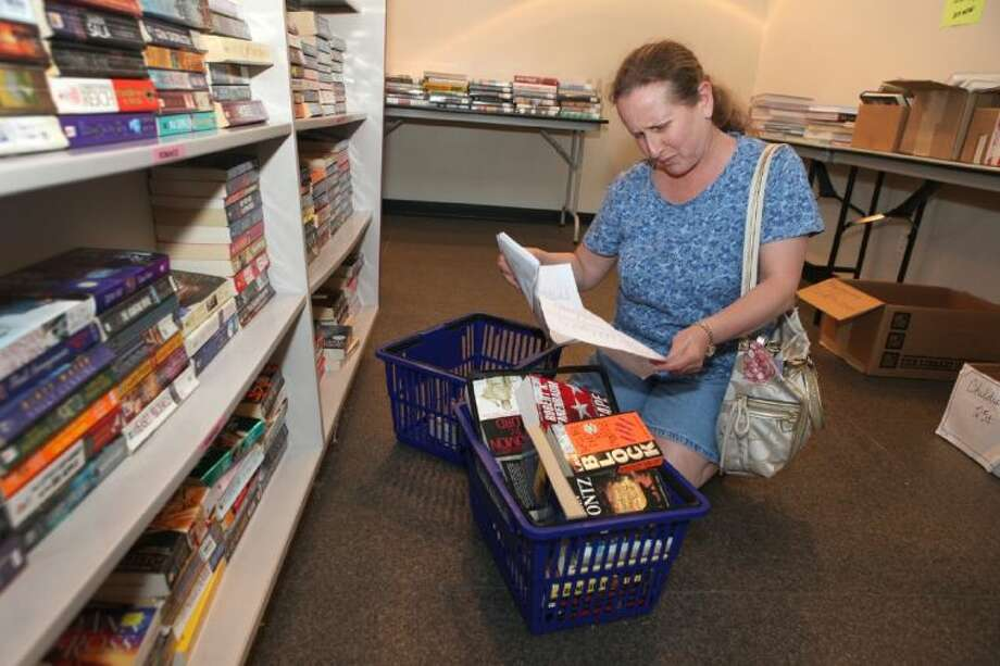 Abbie Gottlieb goes over her list as she buys some books at the Book Sale at George Memorial Library in Richmond on Saturday, July 27. The library is closing between August 4 and September 29, 2013 for renovation of the first floor.
