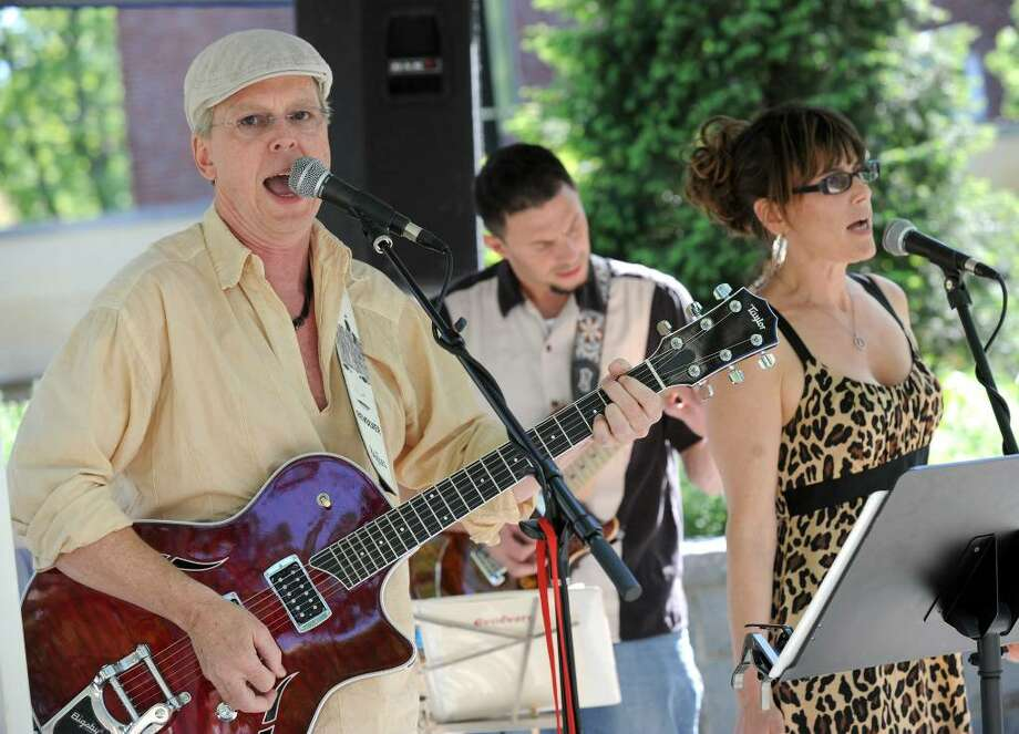 Seth Lefferts, left, of Bethel, with his group Seth Lefferts and the Evolvers, plays in front of the Danbury Library Thursday. Others in the photo are Al Davis of Danbury and Donna Moore of New Fairfield. The event is part of the Connecticut Film Festival. Photo: Carol Kaliff / The News-Times