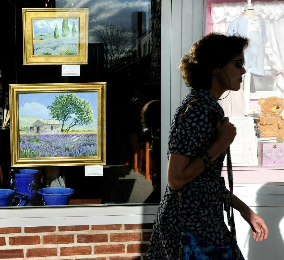 Oil paintings of country settings by artist, Lisa Cuscuna, hang in the window of Hoagland's of Greenwich, during the opening night of Art to the Avenue, organized by the Greenwich Arts Council as an annual spring celebration of art and artists, Thursday evening, May 6, 2010.  Walking past the paintings is artist, Jane Graham of Katonah, N.Y., who works in mixed media and was also showing her work on the Avenue. Photo: Bob Luckey / Greenwich Time