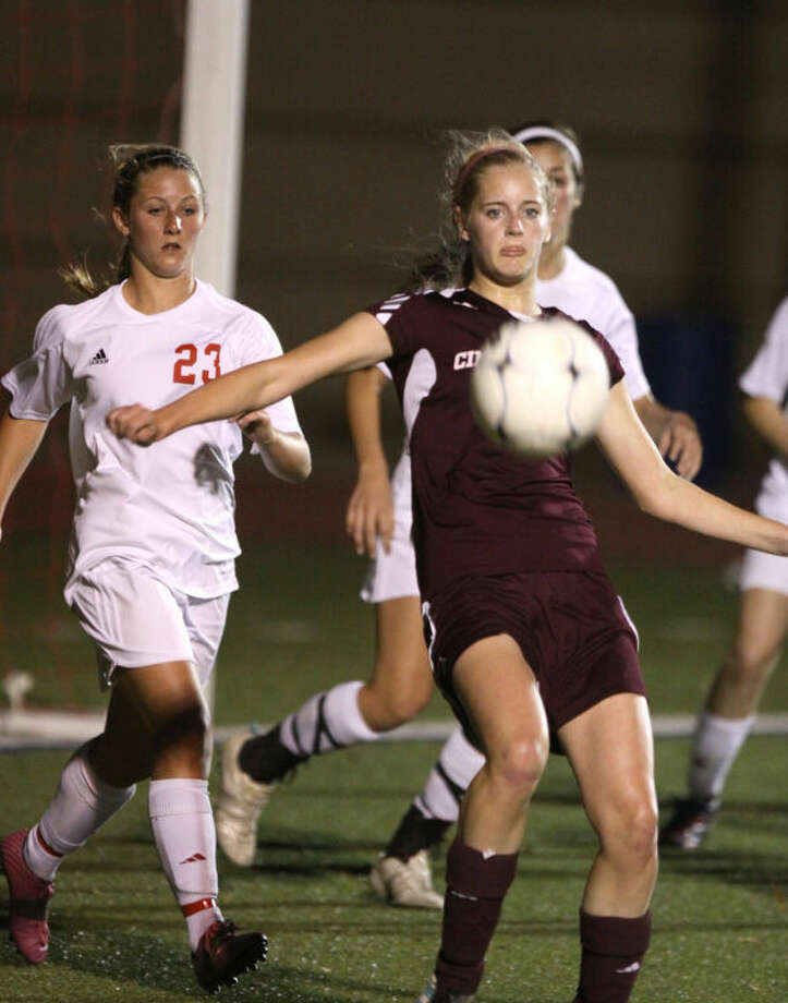 Cinco Ranch's Taryn Siegele traps the ball near the net against Katy's Taylor Niles during their District 19-5A game March 19 at Katy High School. Siegele scored the first goal in a 3-0 victory, concluding an undefeated district championship for Cinco Ranch. Visit www.hcnpics.com for more photos.