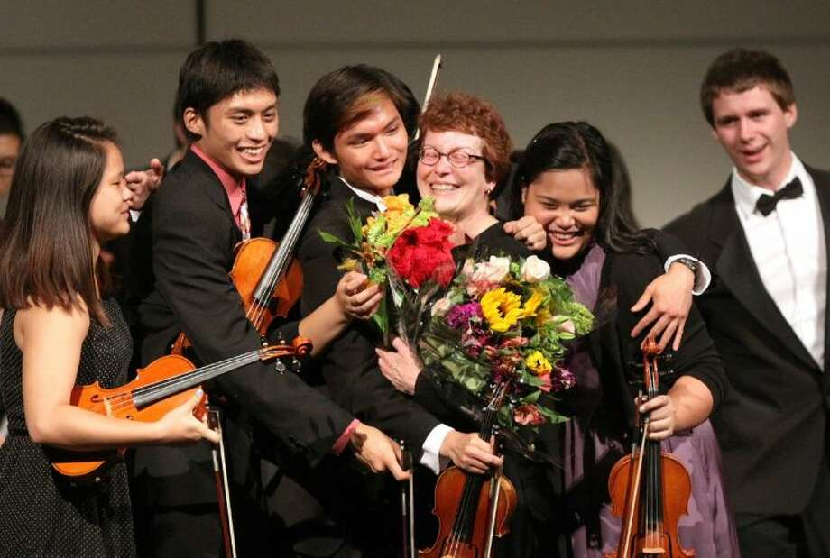 Retiring Bellaire Orchestra Director Kathryn Brown is hugged by her students at the end of the Spring Orchestra Concert on Thursday, May 30.