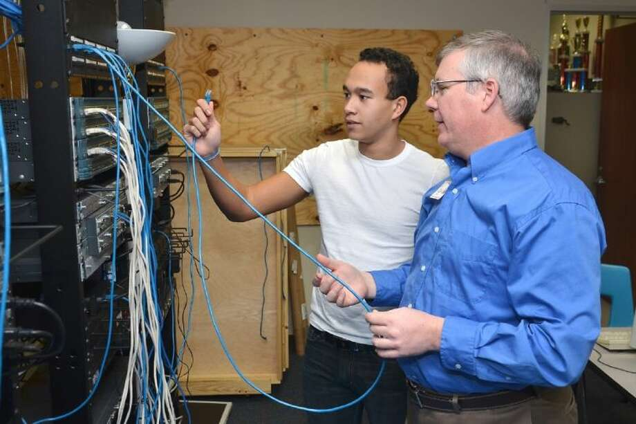 Cypress Creek High School technology teacher Tom Halbert, working with former student Tim Delaforce during an Internetworking Technologies II class last year, has been recognized by the Cisco Networking Academy as an Advanced Level Instructor.