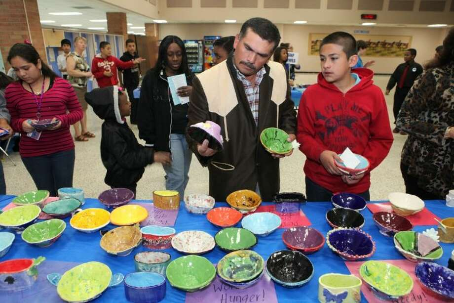 Ines Martinez and his son, Alexander Martinez 12, look for bowls for the Empty Bowls Soup Meal at Lake Olympia Middle School in Missouri City. The school holds the event to support charitable agencies in their efforts to feed the hungry.