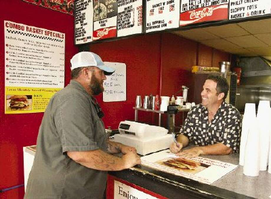Mark DeCosta, of Conroe, left, places an order with Burger Fresh owner Scott Levantino, who regularly works the counter at locations in Conroe and Montgomery.