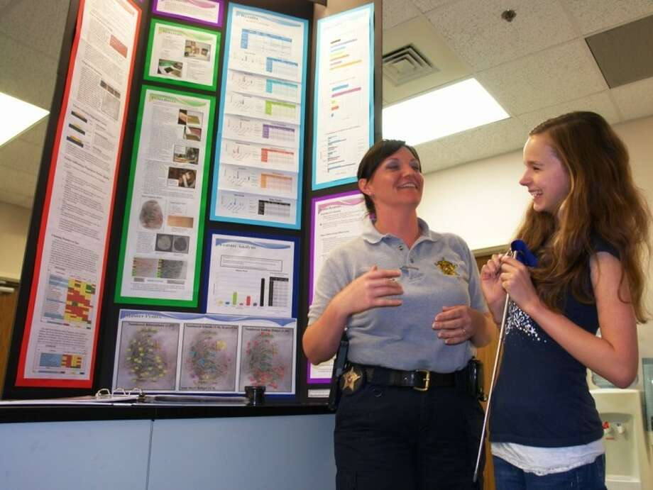Knox Junior High seventh-grader Janet Sonka talks with Crime Scene Investigator Leslie McCauley about her project that won the grand prize at the ExxonMobil Texas Science and Engineering Fair earlier this month.