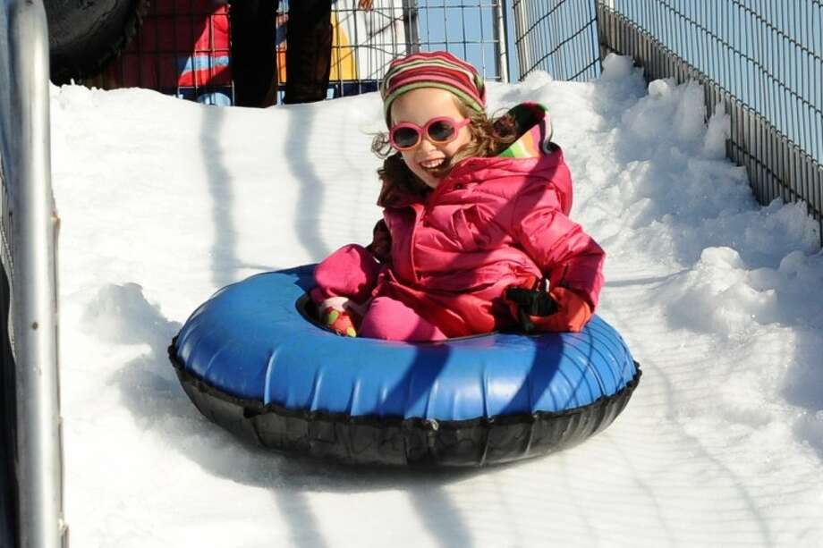 Trinity Bosely enjoys a tube ride down a snow hill during the Pearland Winterfest Saturday, Jan. 28.
