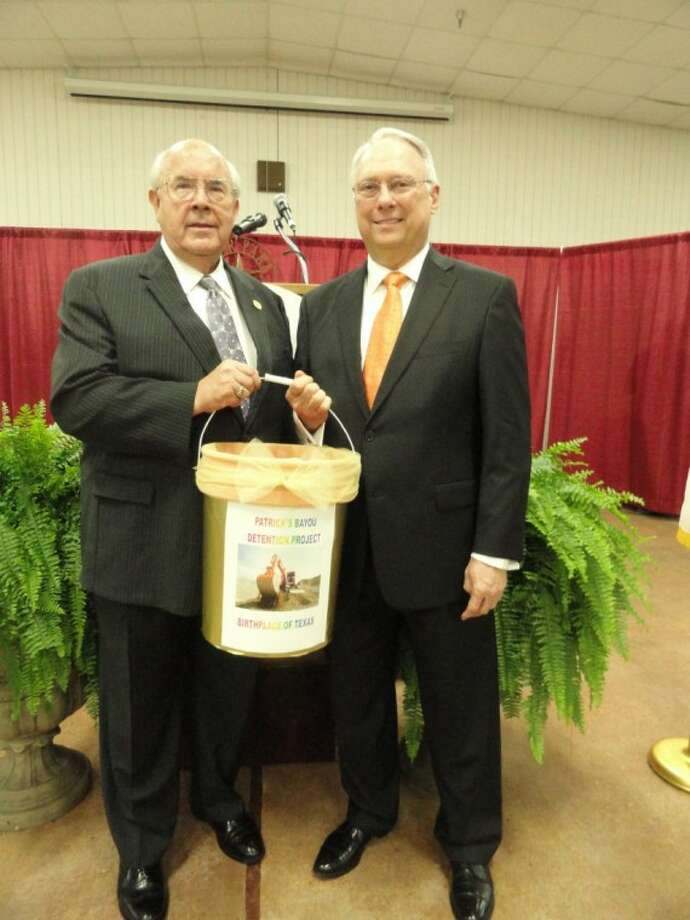 Deer Park Mayor Wayne Riddle (left) and Deer Park Chamber of Commerce Chairman of the Board Ray Landers (right) hold the first bucket of dirt out of the Patrick's Bayou Detention Basin during Thursday's annual State of the City address.
