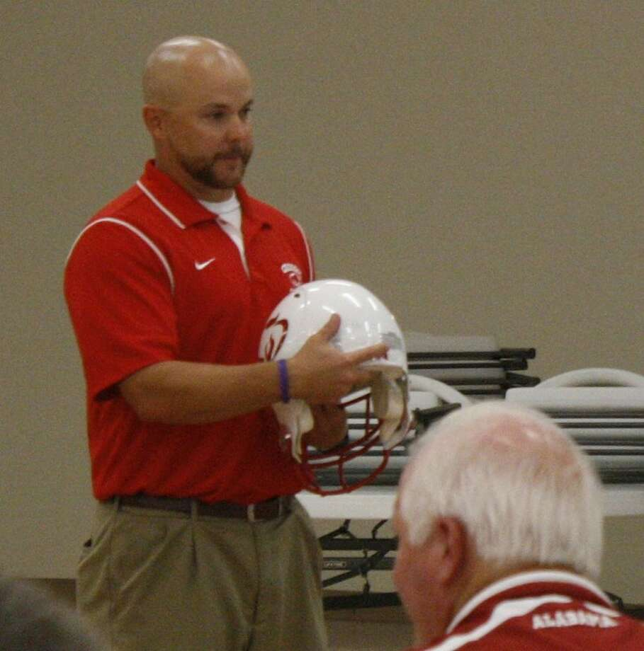 Crosby football coach Jeff Riordan displays the new helmets the Cougars will wear in his first season on the job during a presentation at the Huffman-Crosby Chamber of Commerce luncheon July 19.