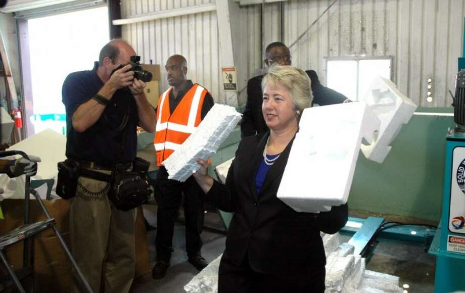Houston Mayor Annise Parker shows the difference between a compacted block of foam (left) and one that's uncompacted.