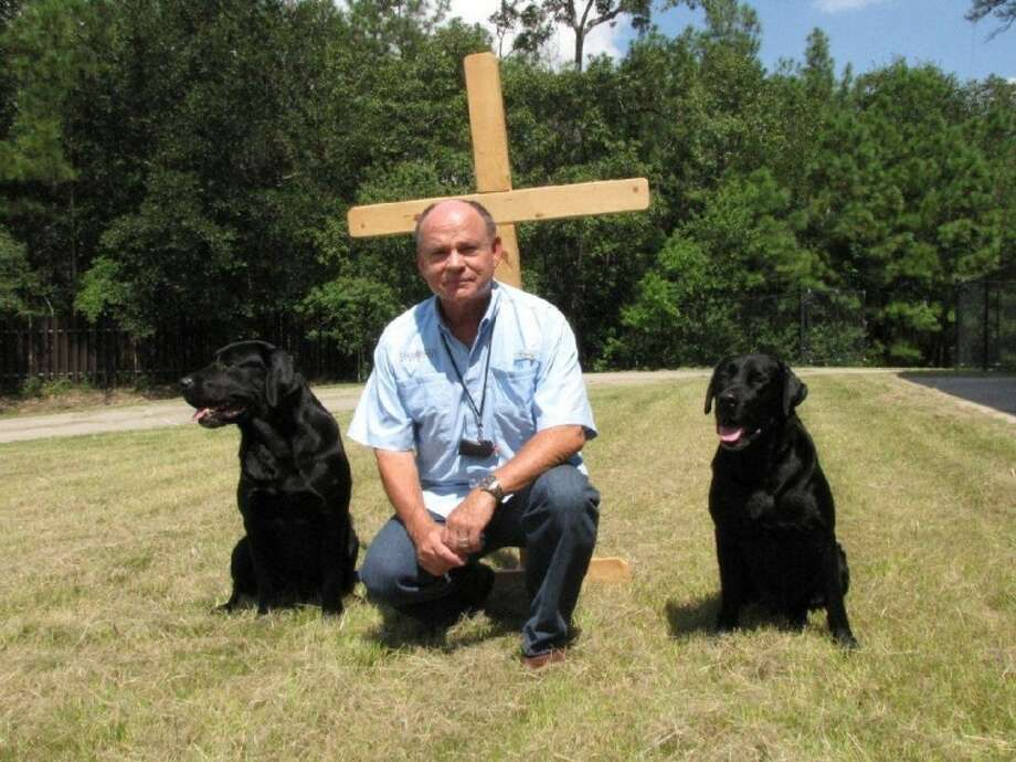 Hank Hough sits with two of his seven Labrador retrievers, Bandera and Profit, who he uses in his Kingdom Dog Ministries demonstrations around the country.