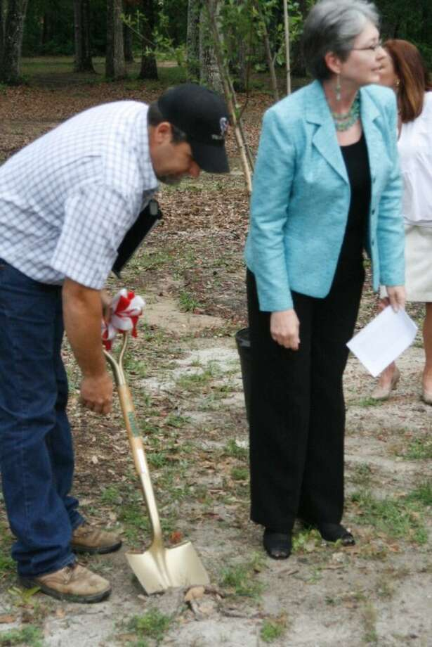 Rusty Lewis, maintenance director at Splendora ISD and a committee member, along with fellow committee member Julie Gillespie turn the dirt for the groundbreaking ceremony April 16 at the district's Outdoor Education Center.