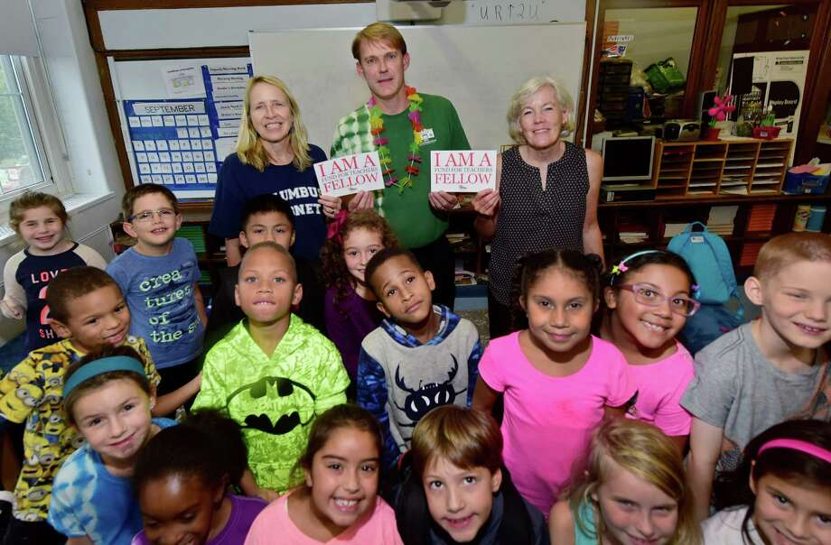 Columbus Magnet School teachers Lauren Baker, Smith Mowry and Jennifer Imhoff gather with students of Baker's second grade class at the school in Norwalk Friday. The teachers were among 21 in the district who were awarded Fund for Teachers grants and traveled the world during the summer as part of their professional development projects. Photo: Erik Trautmann / Hearst Connecticut Media / Norwalk Hour