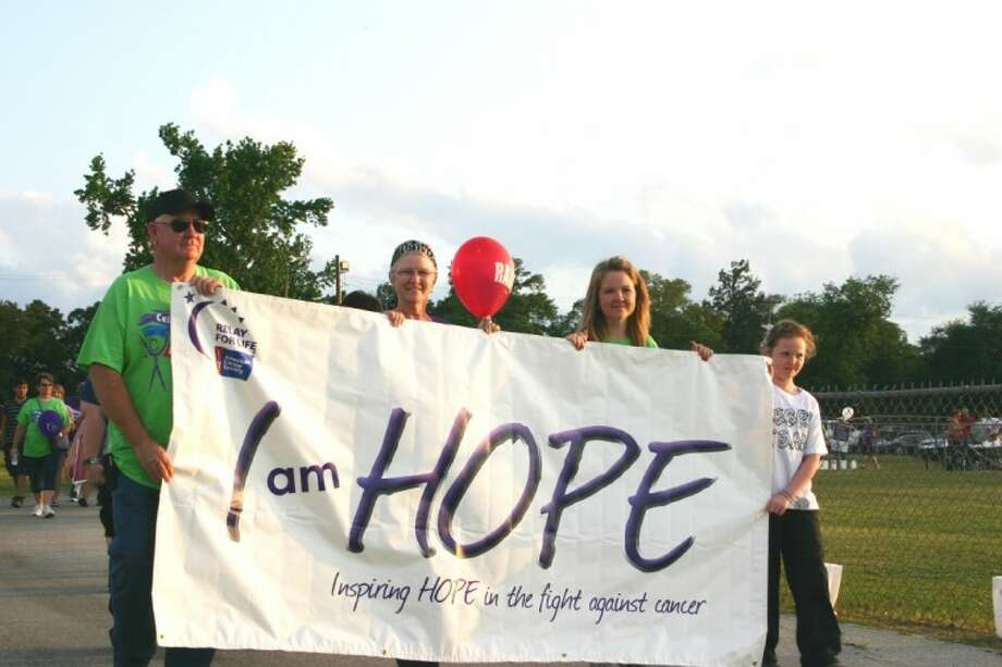 """Carrying a symbolic balloon and holding part of the """"I Am Hope"""" banner, cancer survivor Christine Green walks the first lap of the Relay for Life at Liberty's War Memorial Stadium April 13-14. Joining her in the survivors' lap are, from left, her husband, Ron Green, her daughter, Amy Cobbley, and her granddaughter, Kayla Cobbley. The annual event raises funds for the American Cancer Society."""