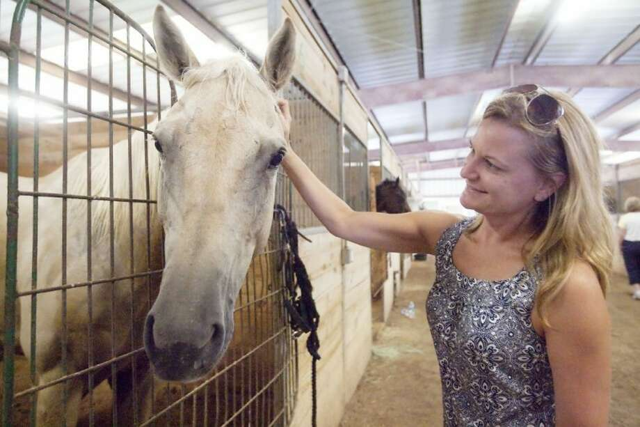 Angela Parr pets her horse, Rico, in the stables at Sam Houston Park in Houston on Friday. Heavy flooding caused Rico to be evacuated from the Cypress Riding School.